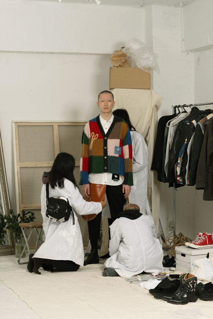 khoki21aw Y cardigan knit パッチワークが特徴のカーディガン。 刺繍は一点一点職人による手作業で作るため、 商品ごとに多少の個体差があります。  今回のシーズンにおいてKHOKIが夢中になったのはアメリカンキルト。 1994年に日本ヴォーグ社から出版された『アメリカ/キルトの世界』に掲載された 数々のキルトから影響を受けた。  特に興味深かったのは本来キルトや民芸品はその土地に欠かせない道具や動物、草木をモチーフにすることが多いのだがこの資料には扇子やインド象、東洋モチーフを配したキルトが沢山見受けられた。 どうやら東洋文化への憧れが一つのムーブメントとしてあった1880年ごろのキルトが多い。  ベースのモヘアニットは正直何色指定しているのはわからないぐらい使用している。 配色の切り替え、刺繍も手刺繍。  敢えて丈を短くしてリブを排除、更に縫い代を外出しグランジ風にまとめているもの。 これは本当に工場様含め一緒に作っているニット企画会社さんのお陰だ。