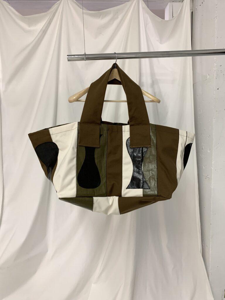 khoki21aw IKE○ bag インラインとしては2回目の登場となった「IKE○ bag」。某家具量販店が販売しているキャリーバッグからインスピレーションを得たアイテム。 私たちが所謂レザーのヴィンテージ品やベークライトのアンティーク品を時に懐かしみ愛でるように、数百年後の世界では今私達の身の周りに溢れているチープなビニール素材もひょっとしたらヴィンテージ品として愛好家の間で出回っているかも、、などと想像しながらビニールと色んな素材の組み合わせを楽しんでいる。パッチワークされている形についてよく何のモチーフなのか聞かれるのだが、正直あまり覚えていない。魚なのか壺なのか、、しかし丸と角が同居している形は落ち着きを与えてくれる気がする。(Matisseに影響されているだけかも、、)